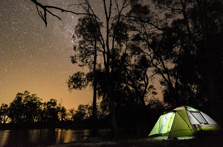 lit up tent beside river in murray river national park campground