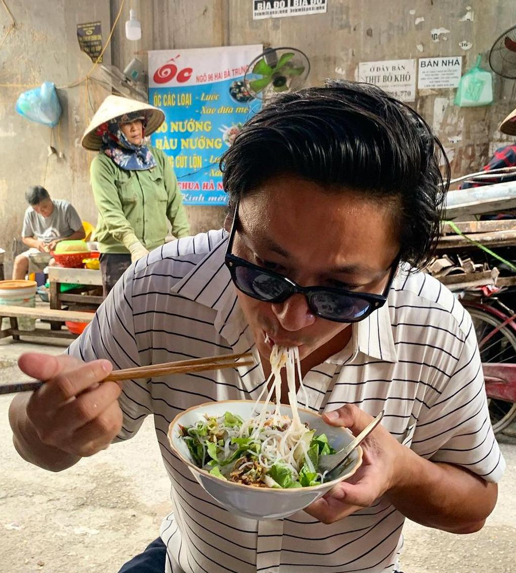 man slurping on bowl of noodles in street