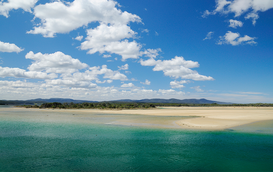 Sparkling blue-green water meets the sandy beach of Mallacoota