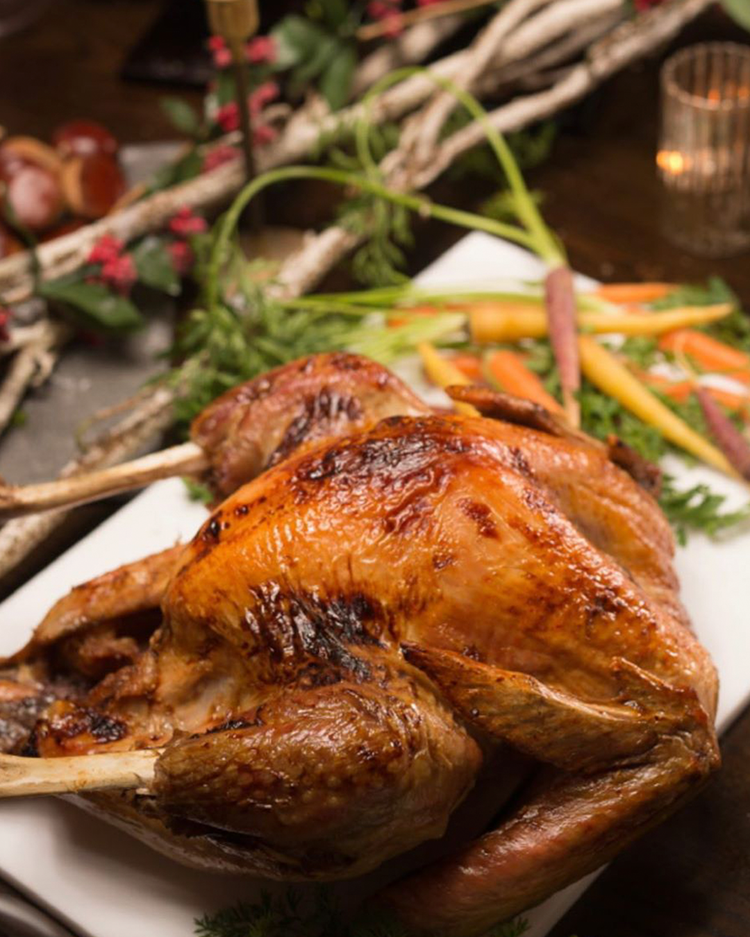 Crispy roast chicken on a white platter with carrots and vegetables in the background.