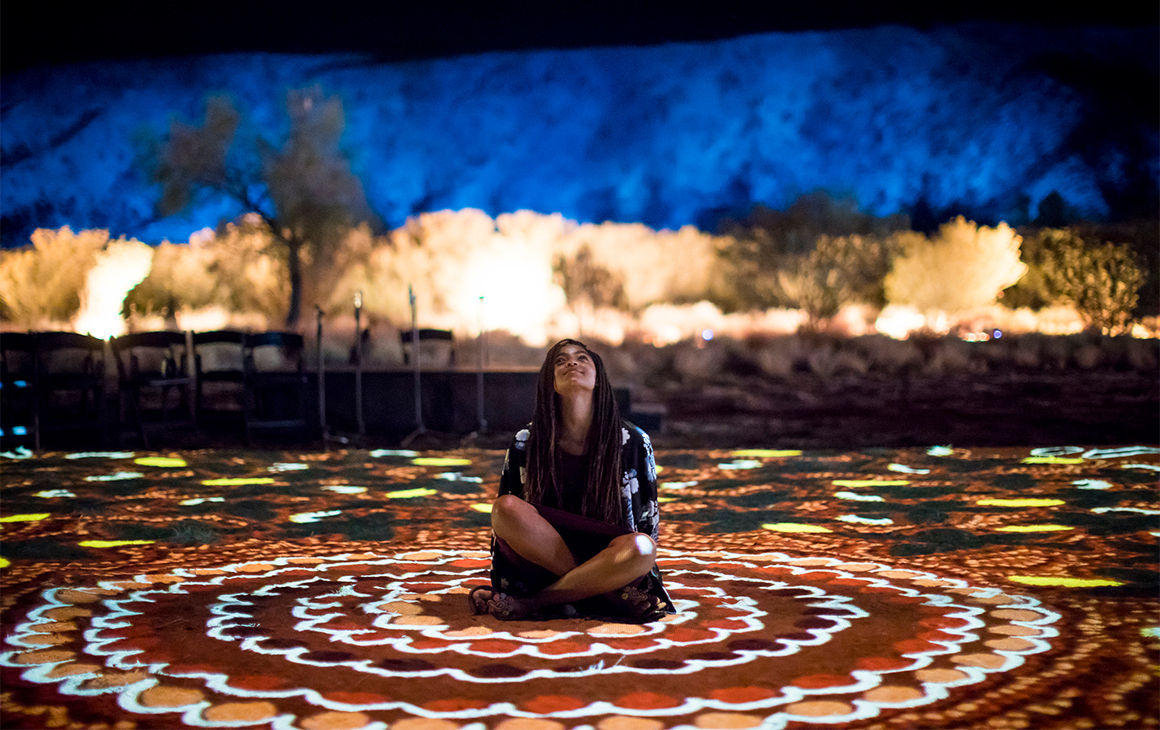 a young girl sits on the ground - which is lit up in various colours - at Alice Springs Desert Park