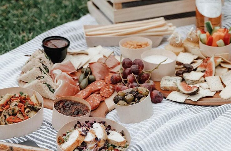 A gourmet picnic hamper on a striped blanket on the grass including rose, a selection of meats, crackers and olives.