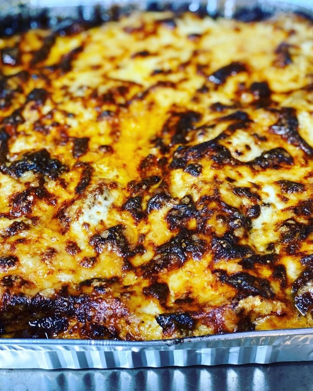 Close up of a large metal sheet pan of lasagne with a bubbling crisp cheese surface.