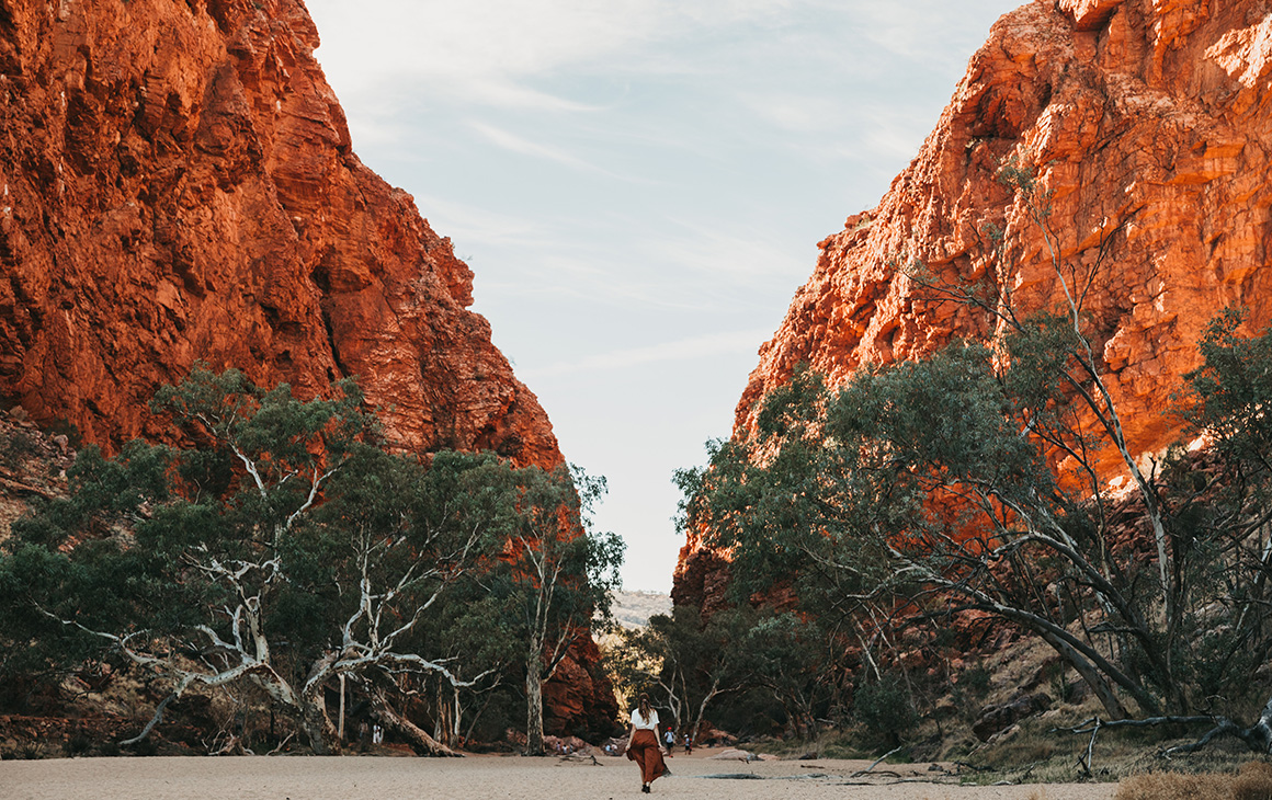 a woman walks between the stunning red rock walls of Simpsons Gap