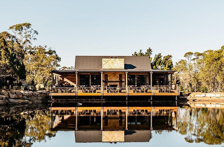 A country-style cottage on a picturesque body of water with a wrap-around verandah.