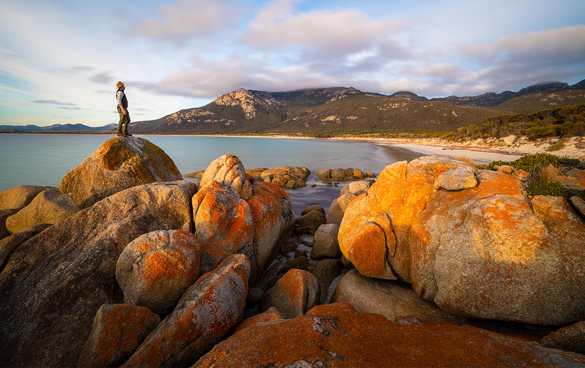 A person stands on orange-tinted rocks on a beach on Flinders Island.