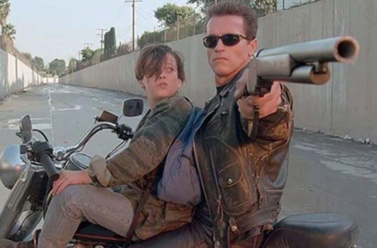 two people on motorbike, one holding gun
