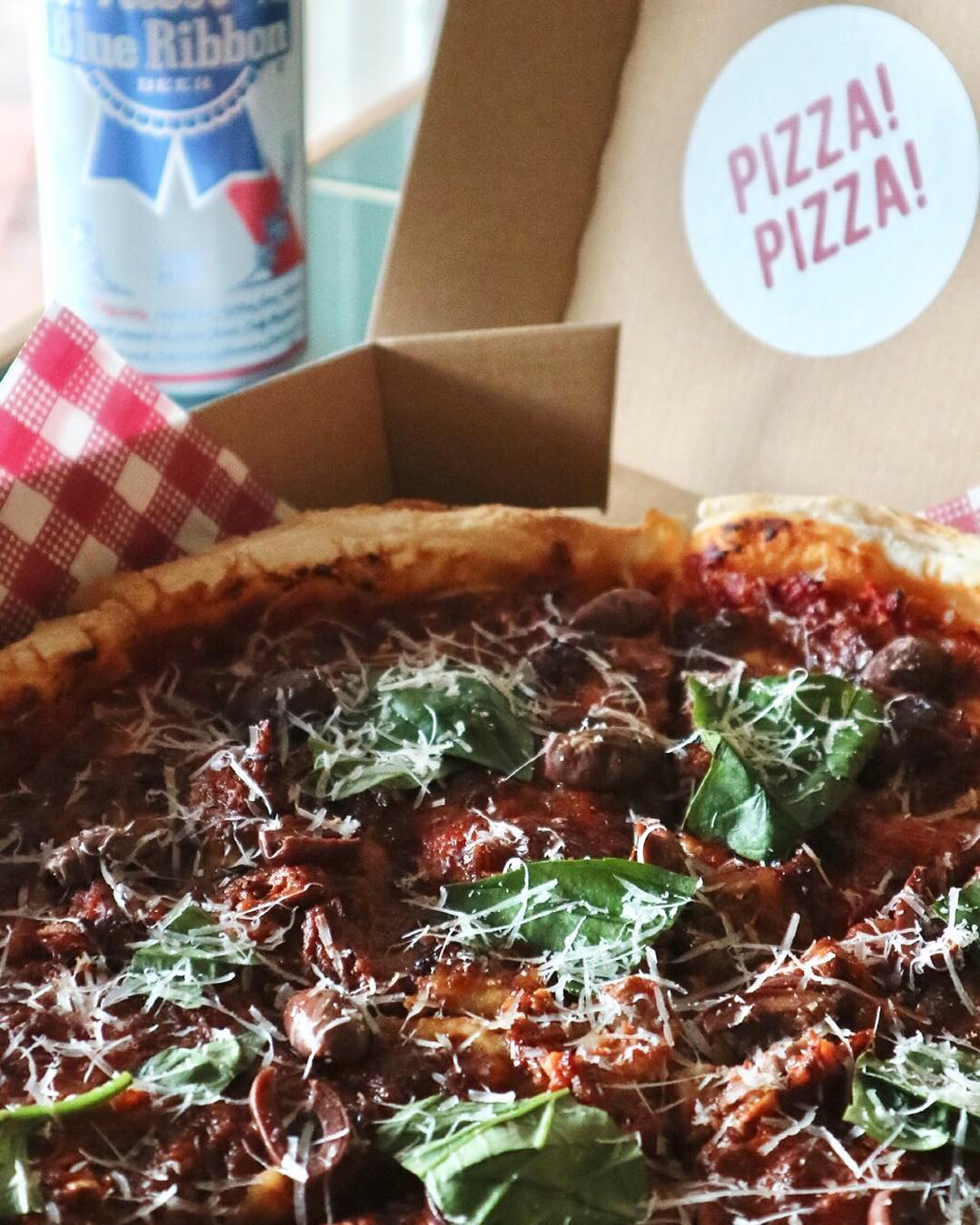 A takeaway pizza box with meaty and cheesy topppings accompanied by a Blue Ribbon beer.
