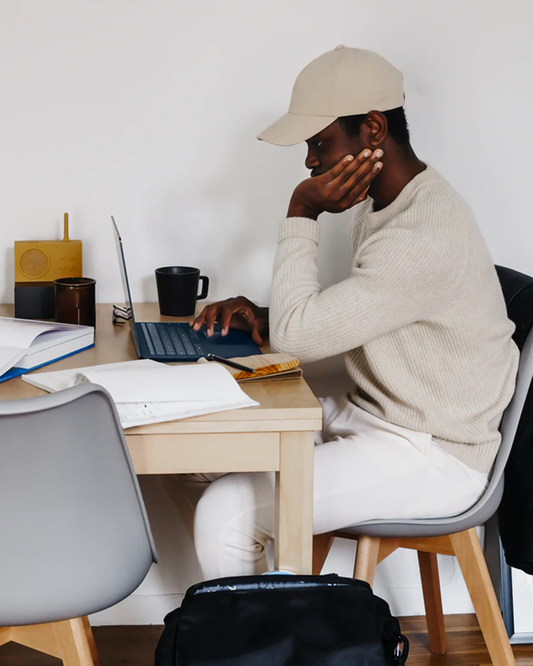 man sitting at desk wearing beige cap and typing