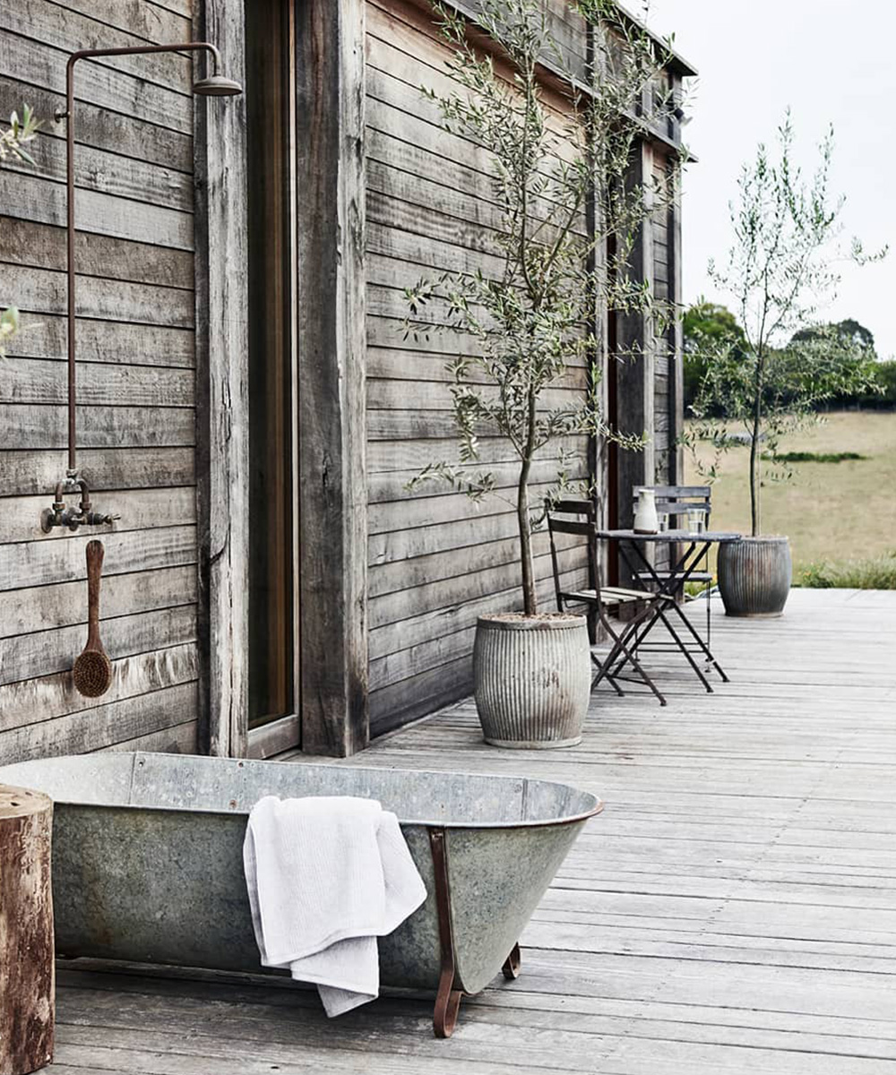 a steel freestanding tub on a wooden deck with a shower above it.