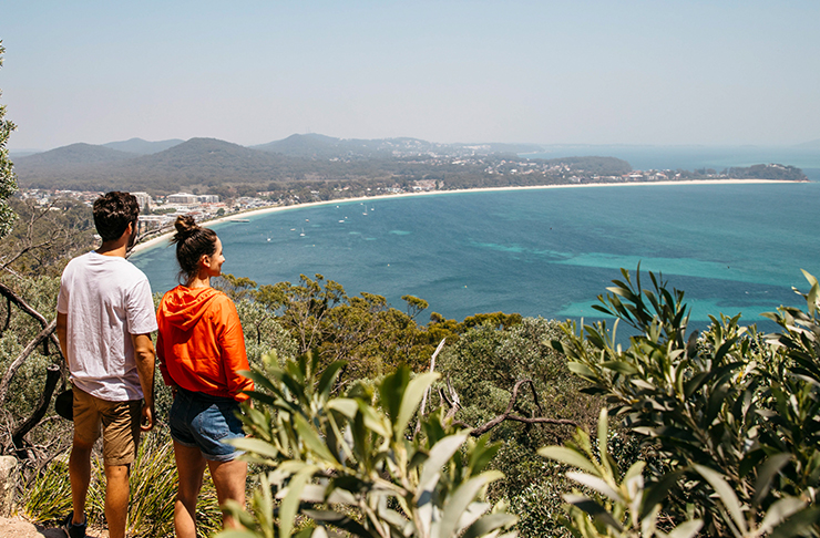 man and woman looking out over port stephens on mountain