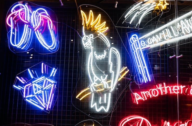 A close up shot of a bright neon wall complete with a neon cockatoo and a neon diamond.