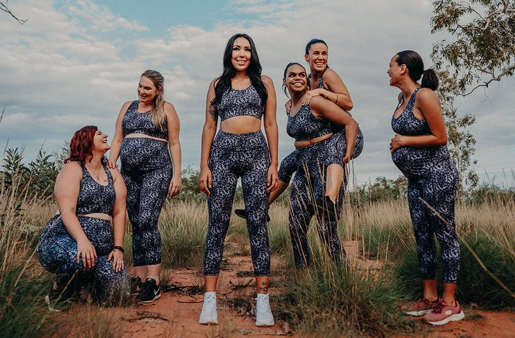 a group of women model activewear on red dirt in the bush of Western Australia