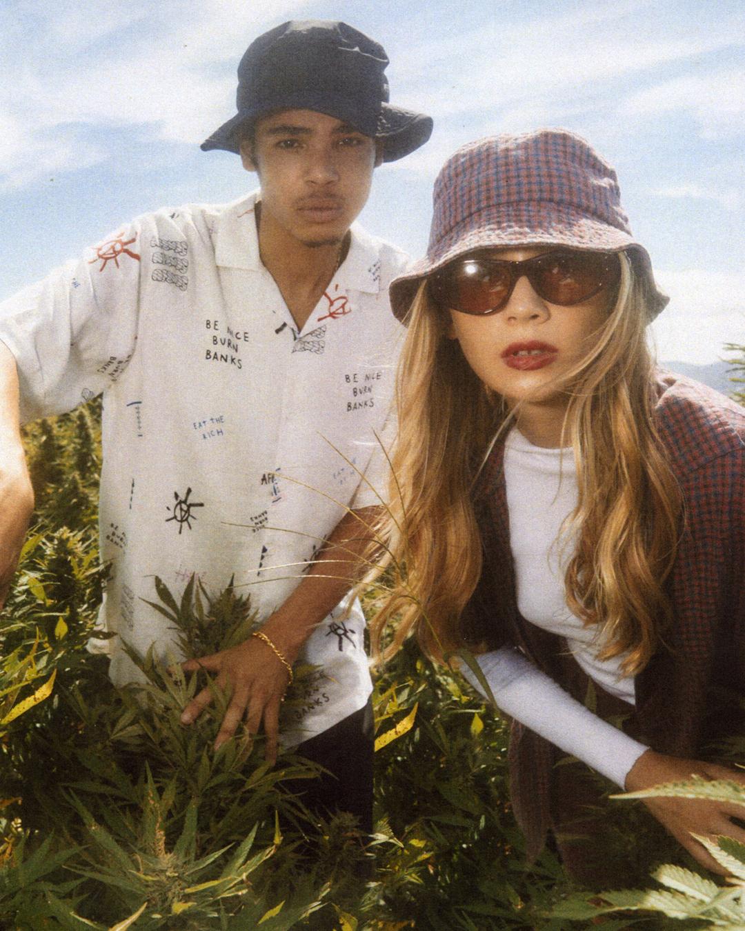 two people in streetwear staring down barrel of camera