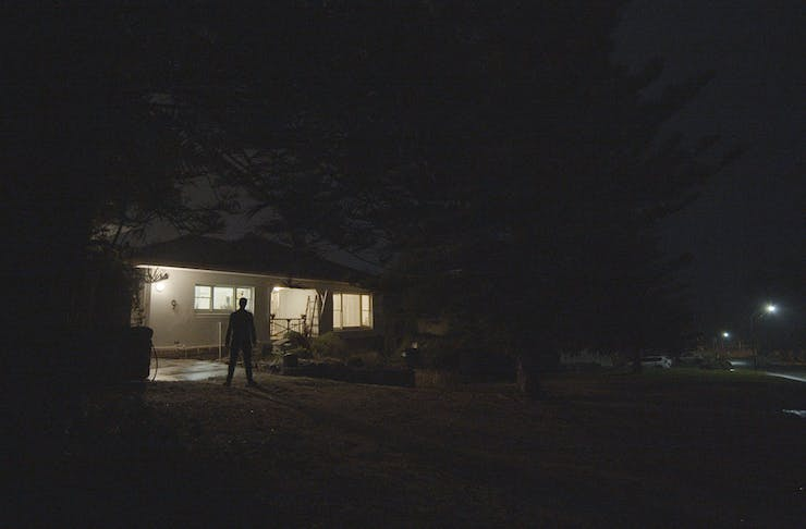 a man stands in front of a house at night.