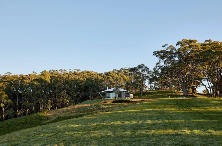 glamping style tent on grassy hill