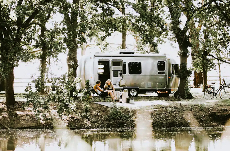 vintage airstream campervan parked near river