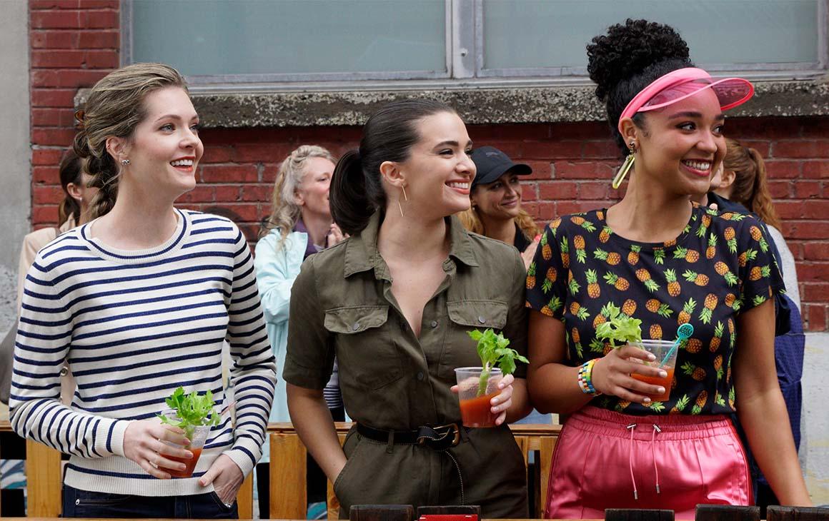 Aisha Dee, Katie Stevens and Meghann Fahy hold bloody marys while cheering on a race.