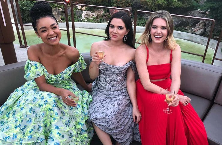 Aisha Dee, Katie Stevens and Meghann Fahy of The Bold Type pose on a couch together in stunning dresses.