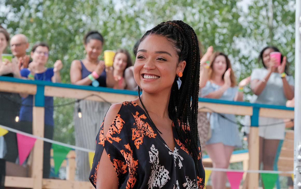 Aisha Dee as Kat on The Bold Type set smiles off camera.