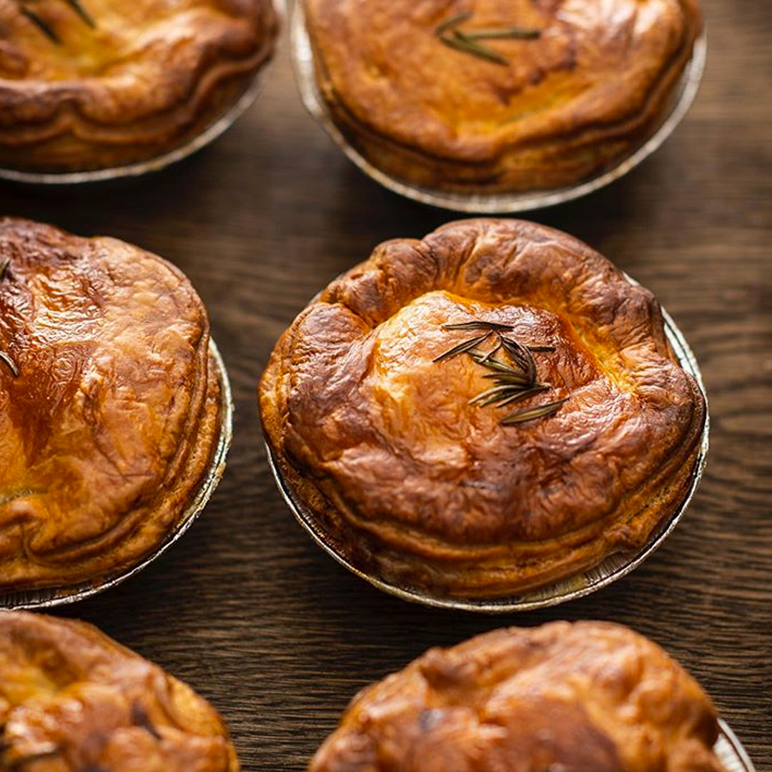 freshly cooked pies on baking try from flour and stone