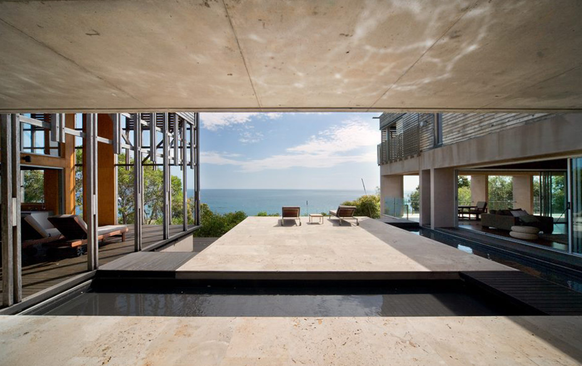 looking out from inside a house is a stunning view of the ocean and an infinity pool.