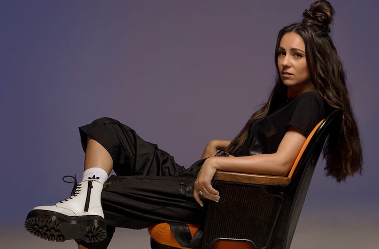 Amy Shark leans back in a chair with her legs crossed.