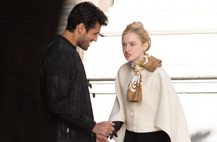 a young woman, dressed in a white coat, yells a man who has a smirk on his face