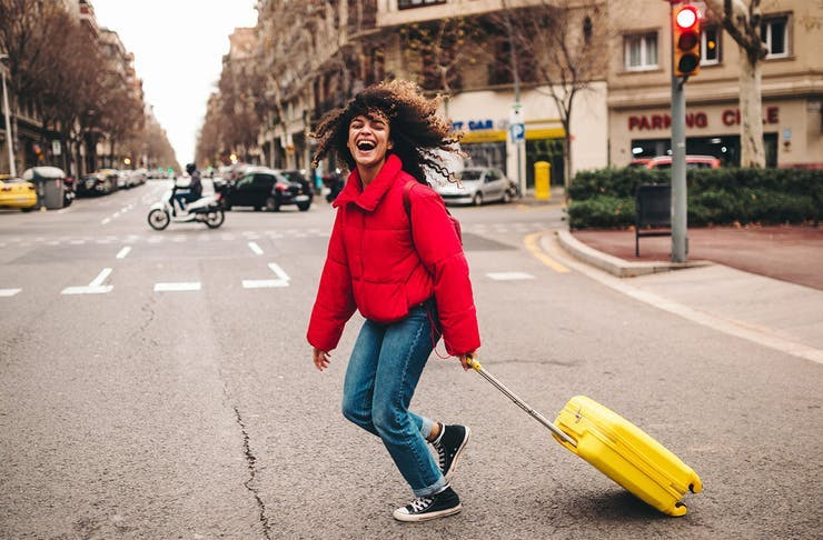 a woman in a red jacket laughs as she pulls a yellow suitcase across the street