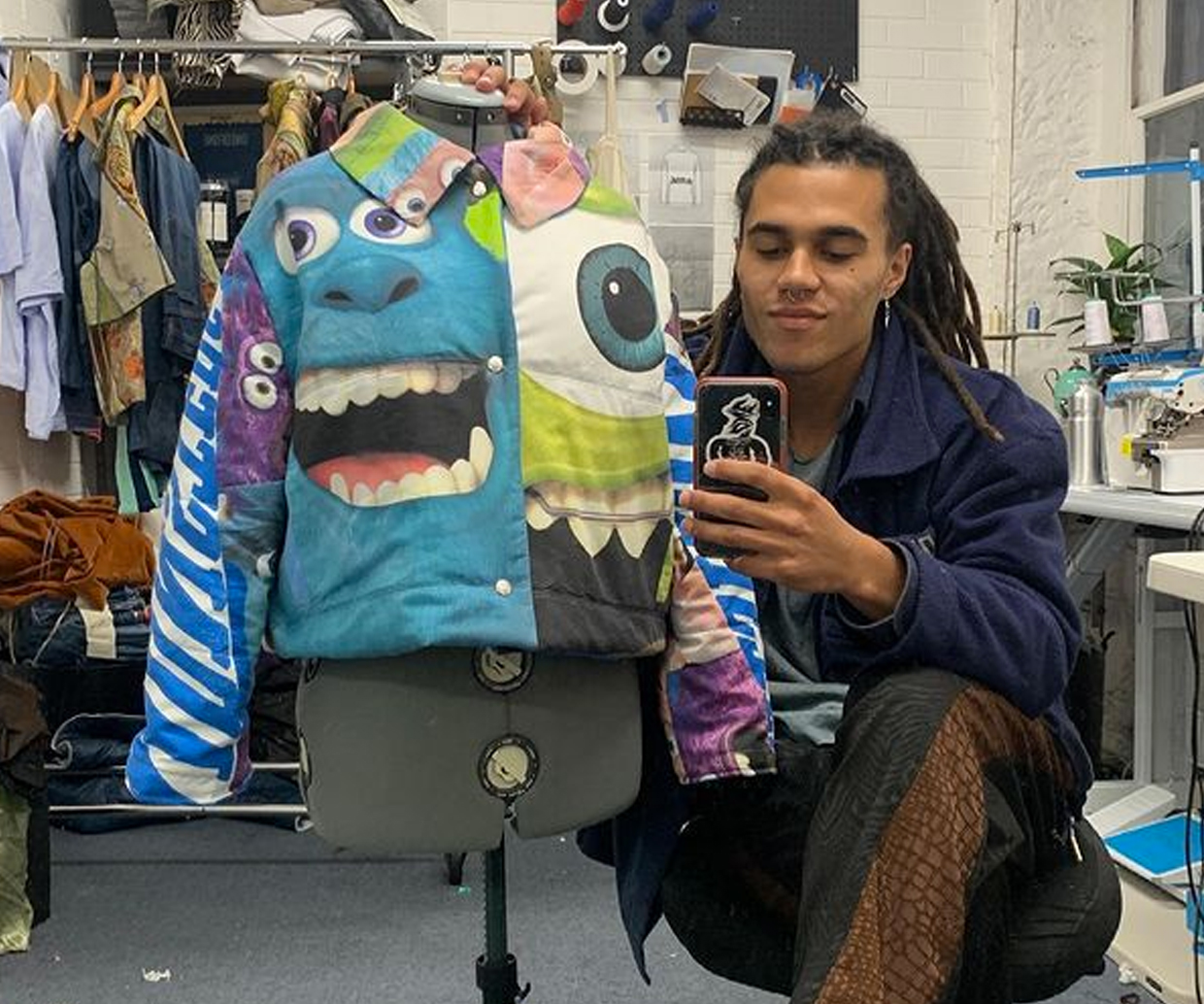 monster print on puffer jacket an dman posing with phone