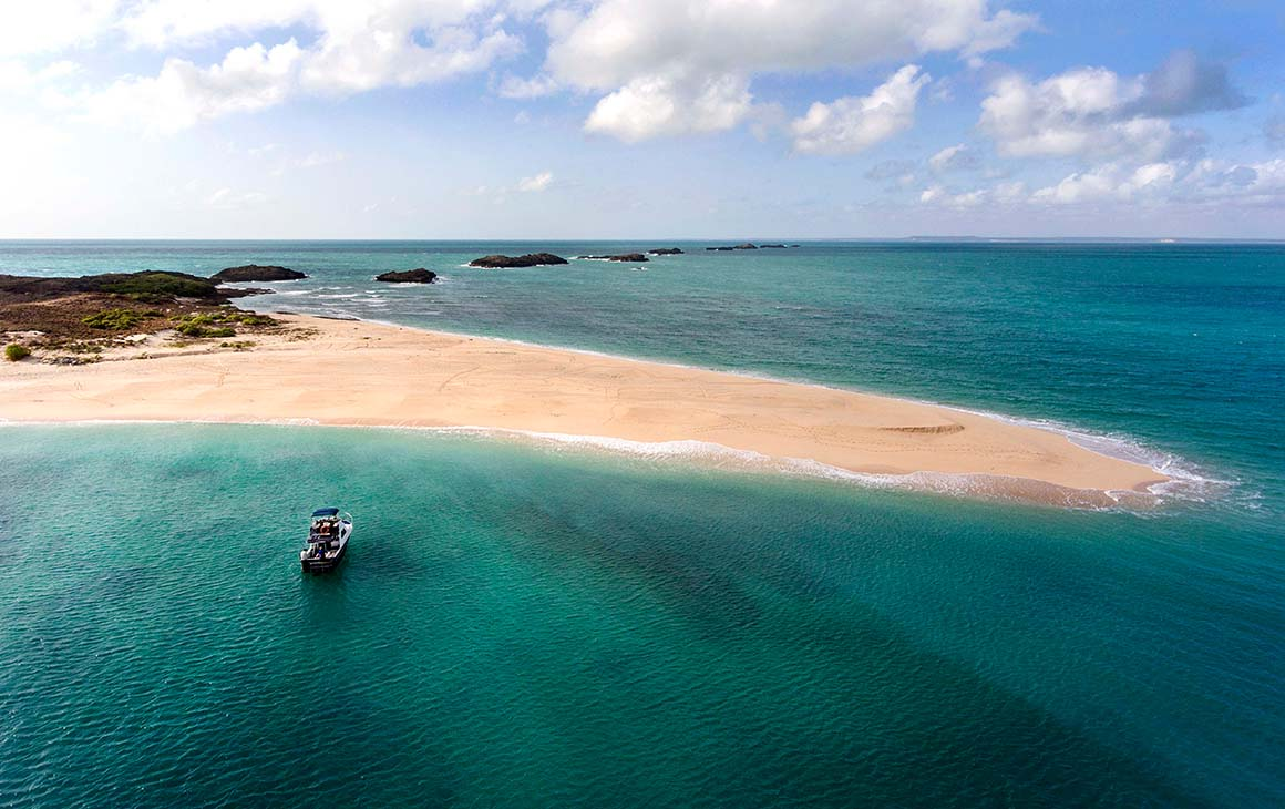 the stunning blue waters of Arnhem Land meets golden sand. A boat floats nearby.