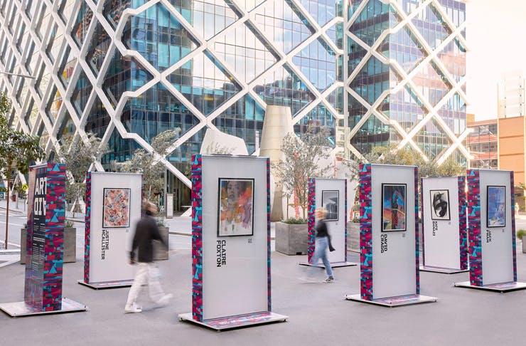 two people walking between outdoor art