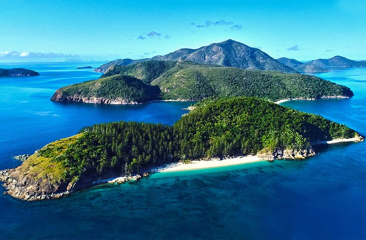 Shaw Island in the Whitsundays is surrounded by deep, navy blue water and is covered in lush, green rainforest.
