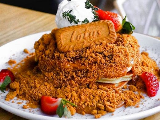 lotus biscuit pancake topped with cookie crumble, fresh strawberries and icecream
