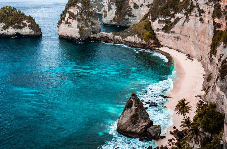 a beach in bali shows off white sand, blue sea and a rugged rocky coastline.