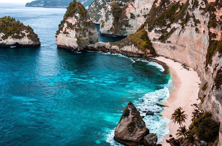 a sparkling blue sea meets a rugged coastline in bali