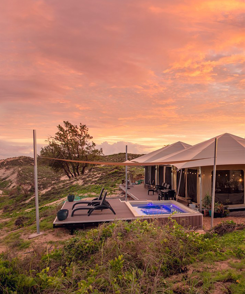 a stunning pink sky lights up over the sea with glamping tents dotted along the sand.