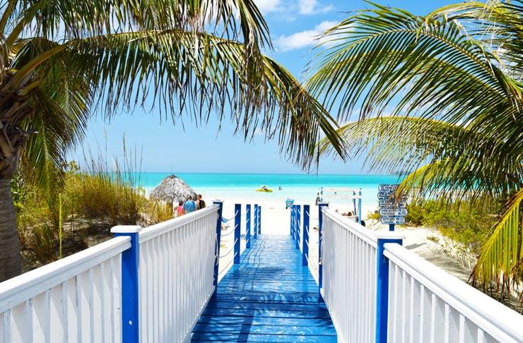 blue boardwalk leading to pristine clear beach in barbados