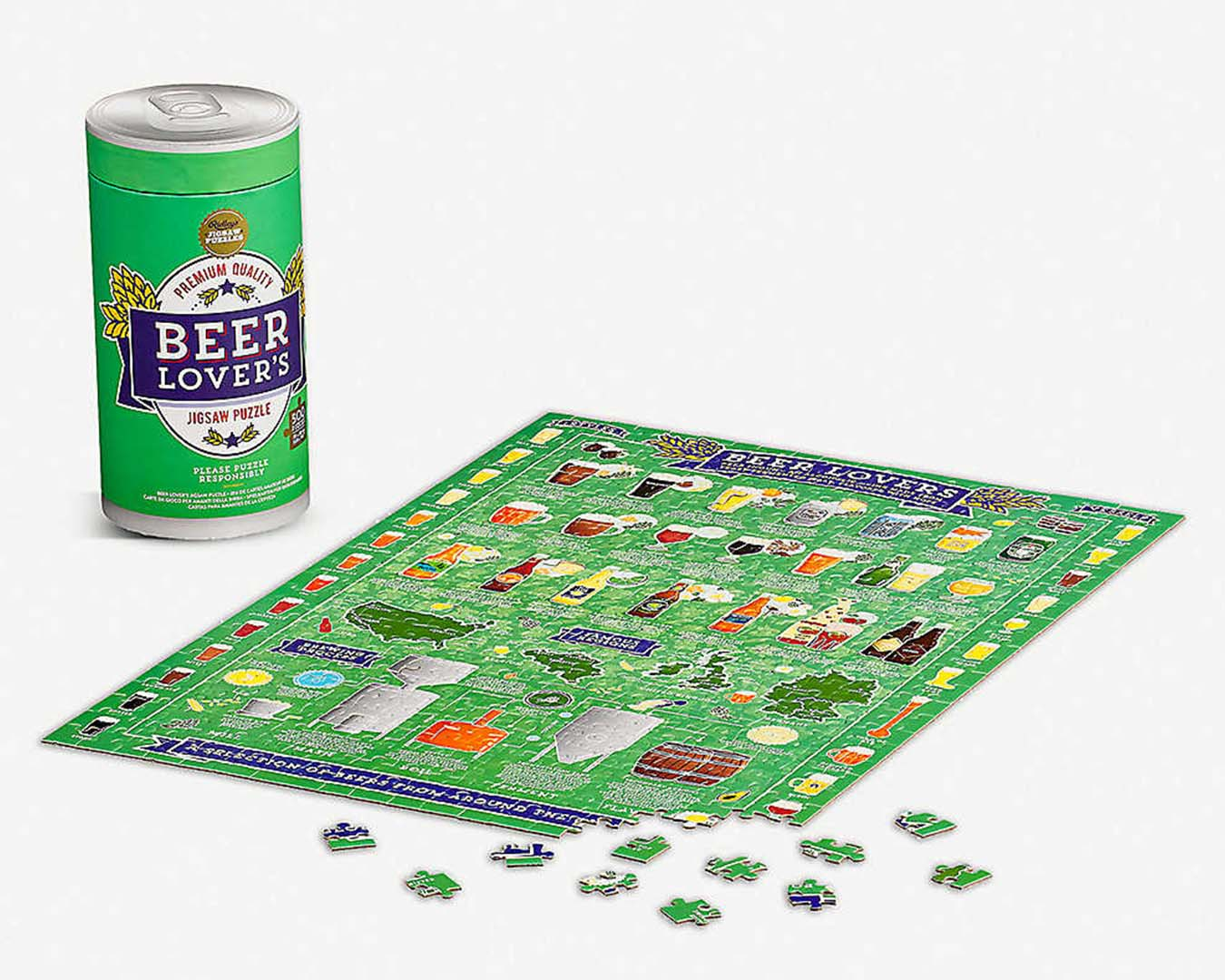 Green, partially made puzzle featuring pictures of beer, sits on a white table. In the background is a puzzle box in the shape of a beer tin.