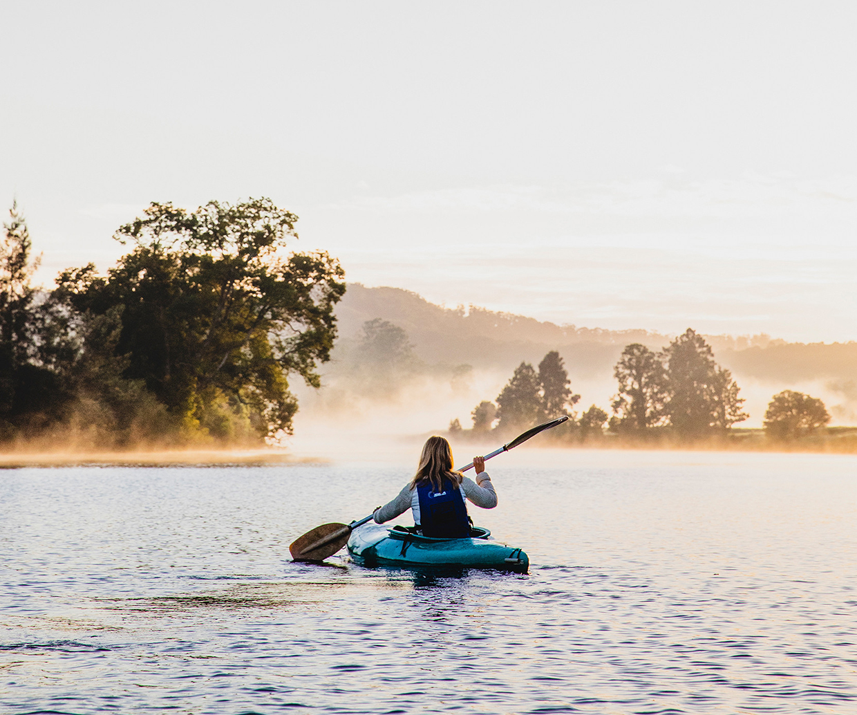 woman in kayak on misty river