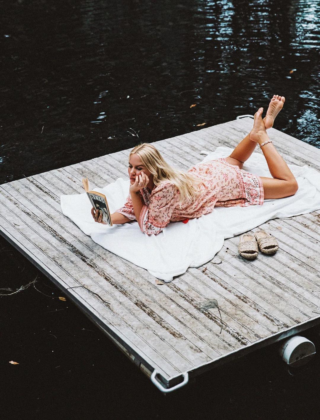 girl lying on bellingen pontoon reading at bellingen tree house
