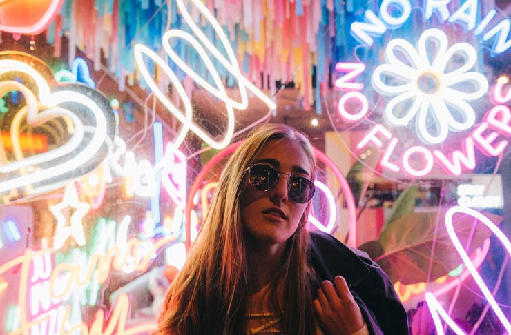 girl with long hair standing in front of neon signs