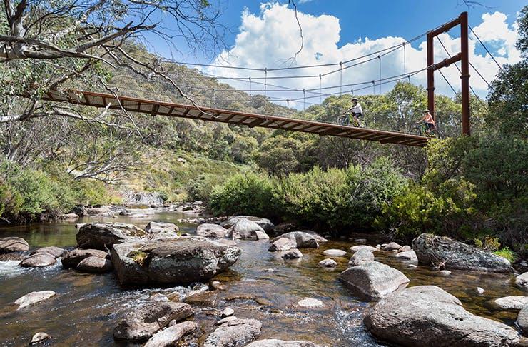 two riding bikes across suspension  bridge over river