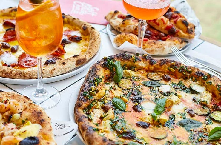 several pizzas on table with aperol spritz