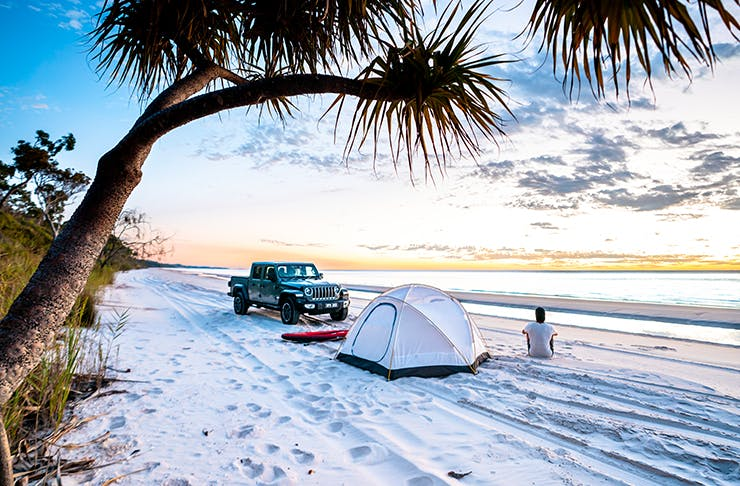 man on beach with tent and 4wd