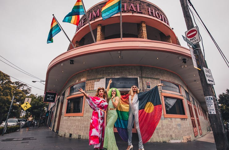 three drag queens out the front of a pub