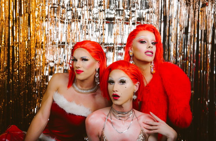 three drag queens in front of silver backdrop