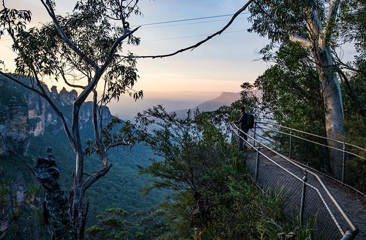man standing on cliff lookout overlooking australia's bushland