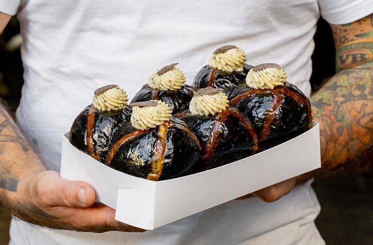 two hands holding box of truffle hot cross buns