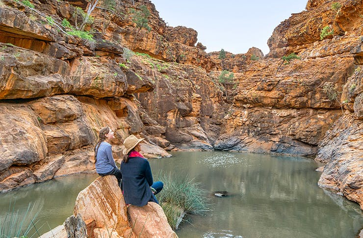 two people sitting on rock looking out onto a bush creek
